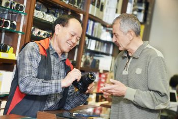 Shop owner explaining camera specs to a potential customer