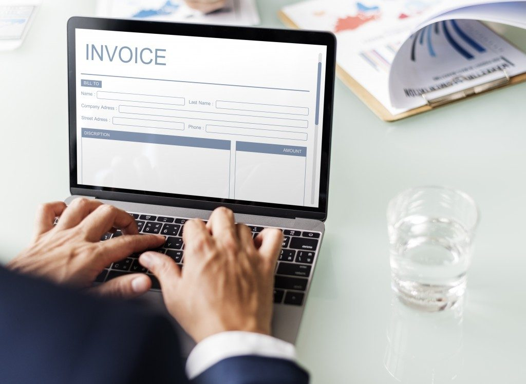 Person working on laptop with invoice on screen
