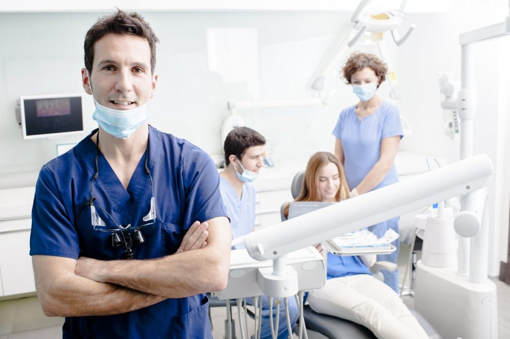 Dentist smiling with his team on the background