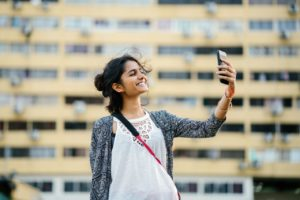 woman smiling using smartphone