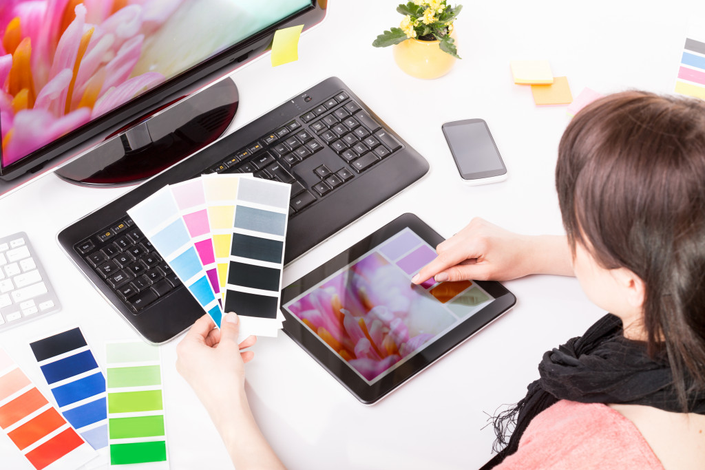 woman holding color swatches and tablet